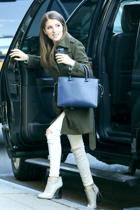 Actress Anna Kendrick styles her ripped up jeans with a classic trench and polished CH Carolina Herrera tote.