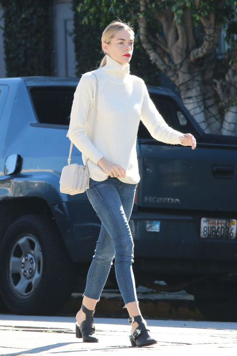 Jamie King looks polished in Mother skinny jeans with a white turtleneck and an eye-catching swipe of red lipstick.