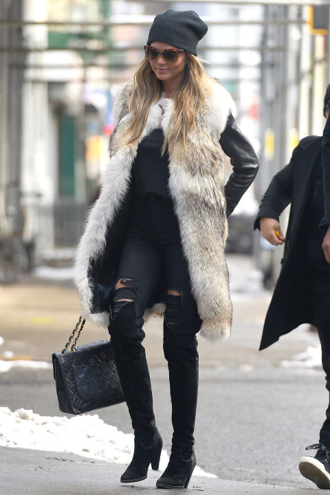 Chrissy Teigen dresses up adds a luxe twist to ripped J Brand jeans with a fur vest and Chanel bag.