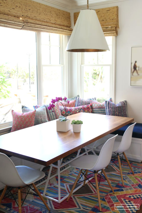Chic meets boho when a wooden table top is accessorized with a single orchid and bench filled with an array of printed pillows.