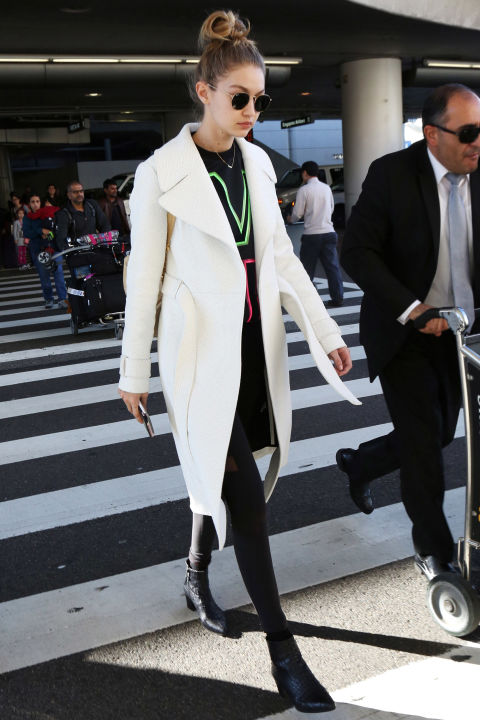 Hadid took to the airport in a winter white A.L.C. topper, paired with a graphic Versace sweatshirt, Beyond Yoga leggings, booties and a top knot.