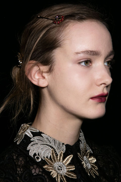 For a modern nod to the '30s, Anthony Turner pulled the hair into a low ponytail, rolled it in toward the nape of the neck and held it in place with jeweled bobby pins, while Val Garland painted on Black Dahlia-inspired lips using NARS Velvet Matte Lip Pencil in Train Bleu and Mysterious Red.<br />
