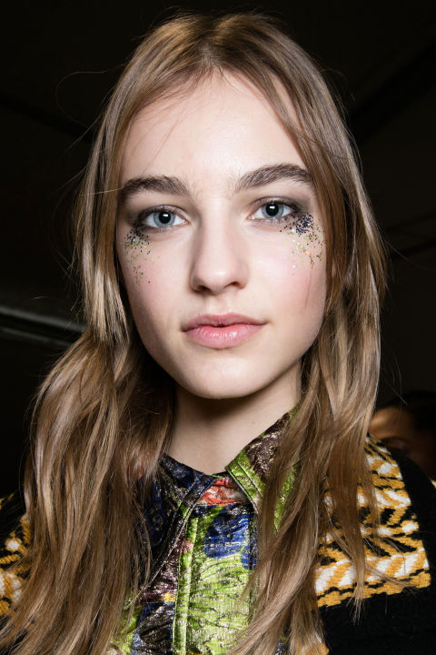 Inspired by the electric colors and metallic embroidery of the Fall collection, makeup artist Wendy Rowe and her team applied 3,000 glitter flecks under the eyes backstage at Burberry for a post-festival vibe.<br />