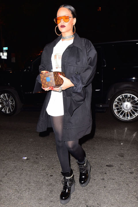 In a black coat, white oversized tee, black tights, wedge booties, a Louis Vuitton box bag, orange sunglasses, crystallized choker and hoop earrings at the Global Citizens afterparty in New York.
