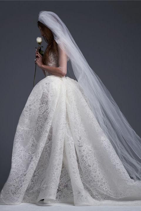 Light ivory macramé lace ball gown with draped skirt and hand placed macramé lace and bridal button accents.