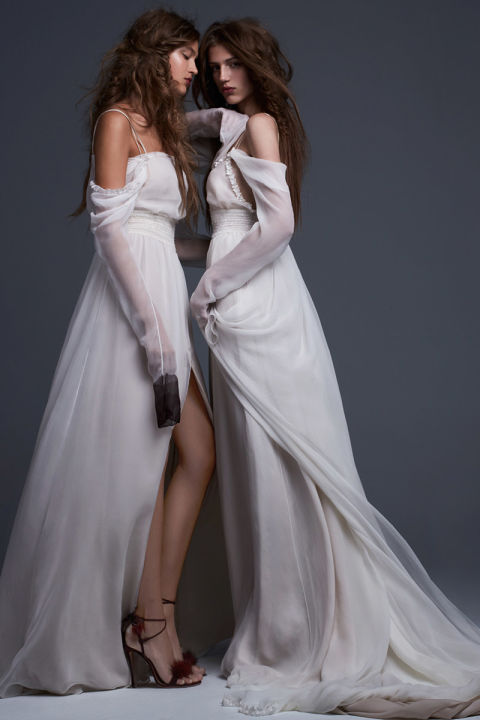 Simona (left): Light ivory silk chiffon off the shoulder gown with straight neckline, draped sleeves and smocked waist detail accented by crimson hand painted sleeves and front slit. Serafina (right): Light ivory silk chiffon off the shoulder gown with V-neck, draped sleeves and smocked waist detail accented by hand applique silk flowers.