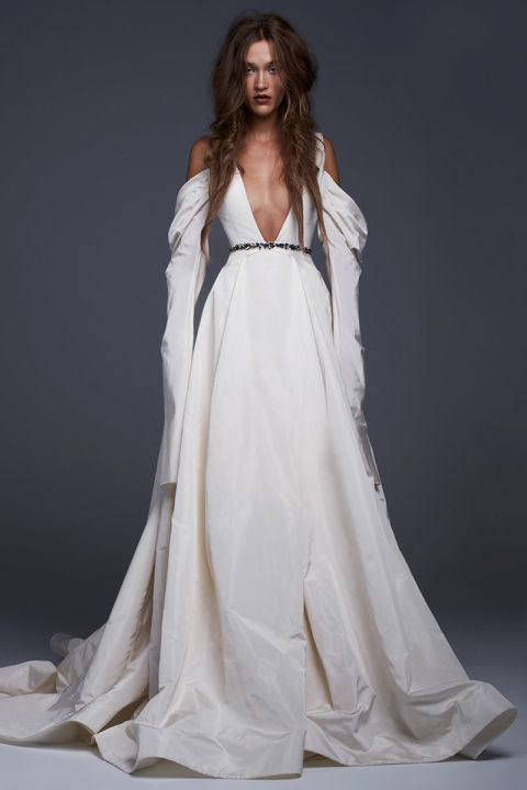 Light ivory silk faille plunging V-neck gown with draped skirt and sleeves and jeweled belt detail.