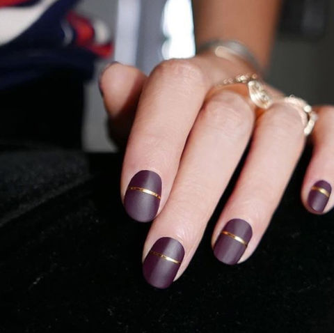 Elevate a burgundy matte manicure with an elegant gilded ribbon through the center.@deborhlippmann