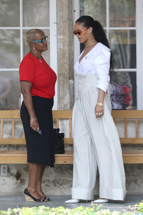 In a white blazer top, ultra high waisted pin-striped trousers, white pointed-toe pumps, assorted rings, a gold watch and '90s-esque orange sunglasses in Barbados.
