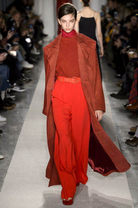 While Roche has become known for her ultra luxe tan, blush and black pieces here she played with shades of red layered under a cool suede trench