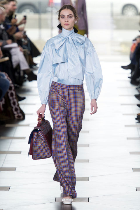 Continuing on the theme of deftly melding traditional female and male fashion tropes, a pussy bow blouse (another nod to Burch's own mom) was paired with plaid pants and a matching plaid briefcase, it's modern prep at its best.