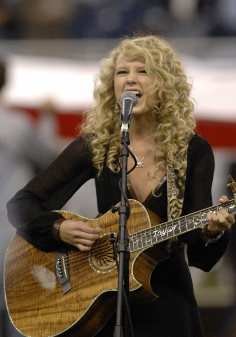 In one of her earliest televised performances, Taylor Swift belted out the National Anthem at the Detroit Lions/Miami Dolphins Thanksgiving Day game in 2006—complete with her acoustic guitar and old-school curls.